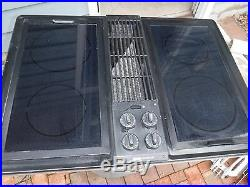 Jenn air downdraft cooktop with black glass burners and grill unit